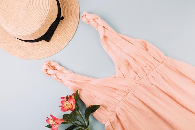 Flores cerca del sombrero y el vestido