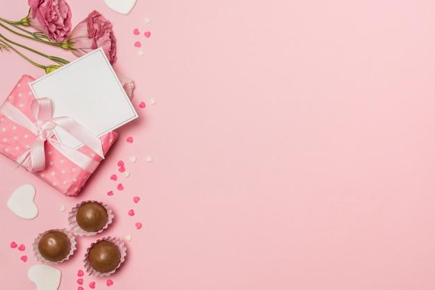Flores cerca de tarjeta postal en caja actual y caramelos de chocolate.