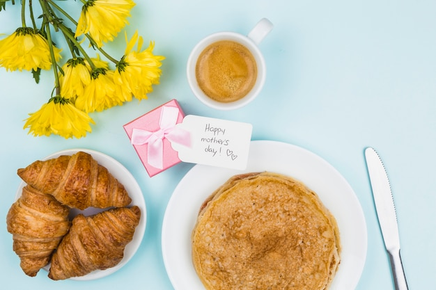 Flores cercanas al presente con etiqueta y platos con crepes y croissants.