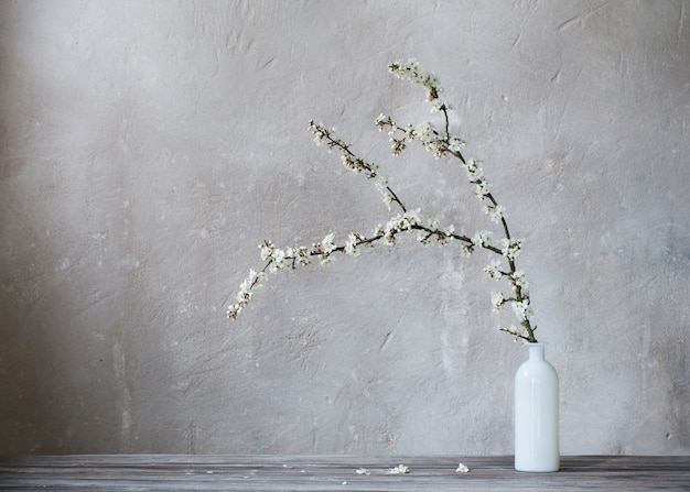 Flores de cerezo blanco en florero sobre fondo gris antiguo