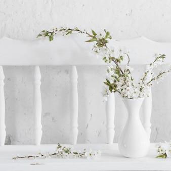 Flores de cerezo en florero sobre fondo blanco.