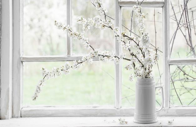 Flores de cerezo en jarra blanca en el alféizar de la ventana
