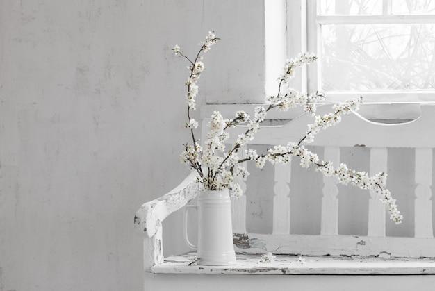 Flores de cerezo en jarra blanca sobre banco de madera antiguo