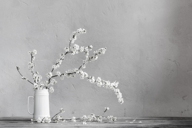 Flores de cerezo en jarra blanca sobre mesa de madera antigua