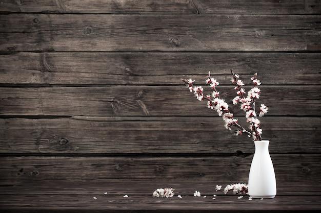 Flores de cerezo en jarrón sobre fondo de madera oscura.