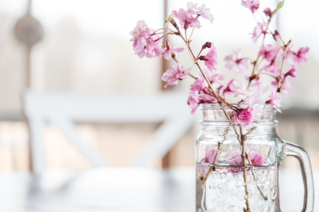 Flores de cerezo y ramas en un vaso de agua sobre la mesa bajo las luces