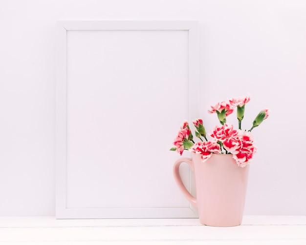 Flores de clavel en florero con marco de fotos vacío en mesa