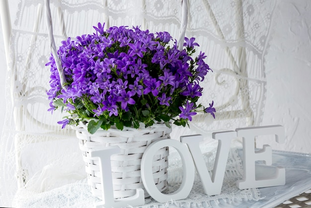 Flores de color púrpura en una canasta blanca y la palabra amor
