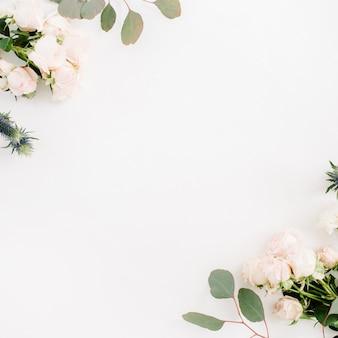 Flores color de rosa beige, flor de eringio, ramas de eucalipto sobre fondo blanco. endecha plana, vista superior