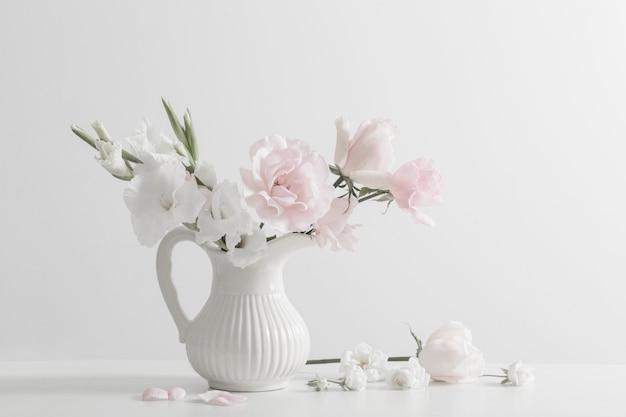 Flores de color rosa y blanco en florero sobre fondo blanco.