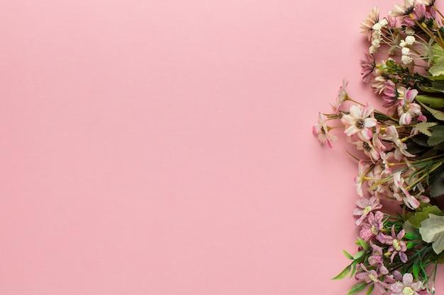 Flores de color rosa y hojas en el lateral