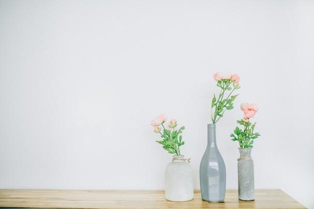 Flores color de rosa rosa pastel en jarrones cerca de blanco.