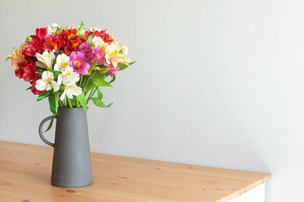 Flores de colores en un jarrón de cemento sobre una mesa de madera
