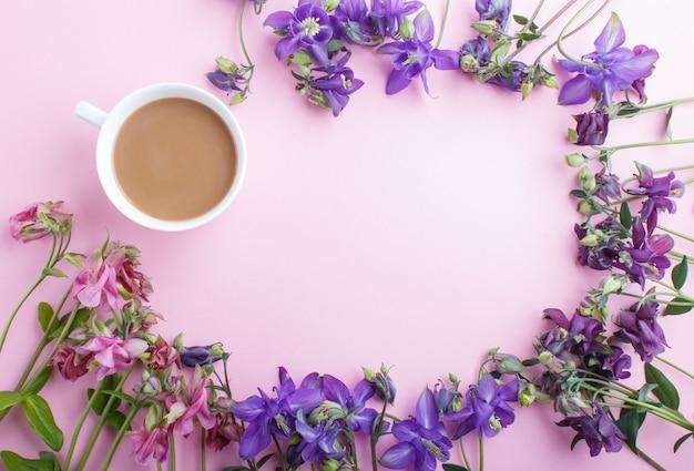 Flores columbine rosa y púrpura y una taza de café, fondo de vista superior con copyspace