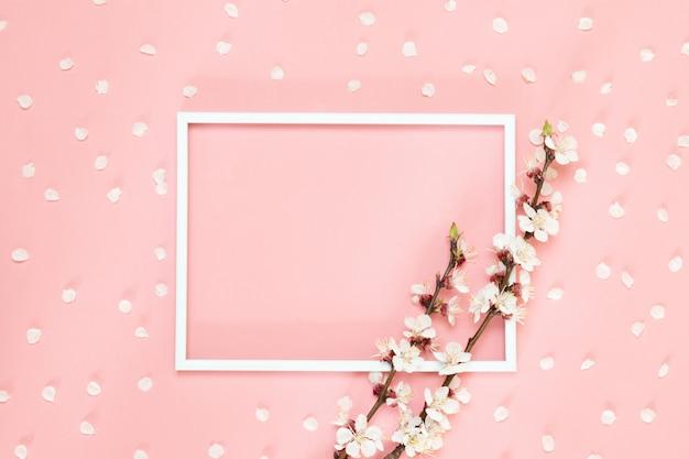 Flores de composición creativa. marco en blanco de la foto, flores rosadas en el fondo coralino vivo, espacio de la copia.