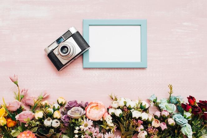 Flores con marco azul y cámara vintage
