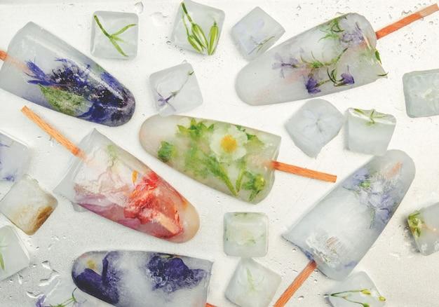 Flores congeladas en cubitos de hielo y helado en un palo. enfoque selectivo