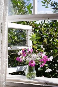 Flores del cosmos en jarrón de vidrio en el alféizar de la ventana en el campo