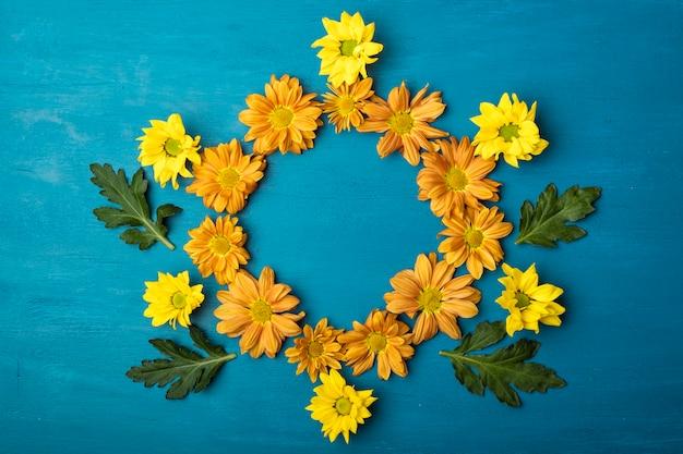 Flores de crisantemo con espacio de copia. marco redondo de flores sobre un fondo azul.