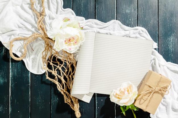 Flores con cuaderno vintage vacío y regalo