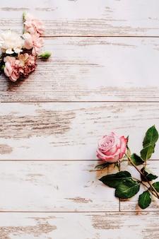 Flores de clavel y rosa en la mesa de madera vieja