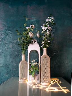 Flores decorativas en jarrones sobre la mesa con pared azul