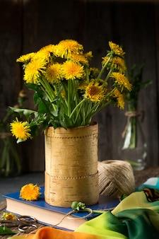 Flores de diente de león en superficie rústica bodegón vintage
