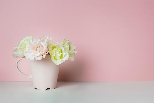 Flores elegantes en taza de té