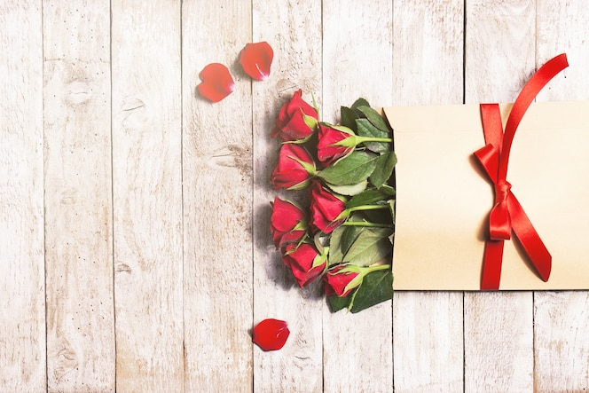Flores en un sobre de papel con pétalos alrededor