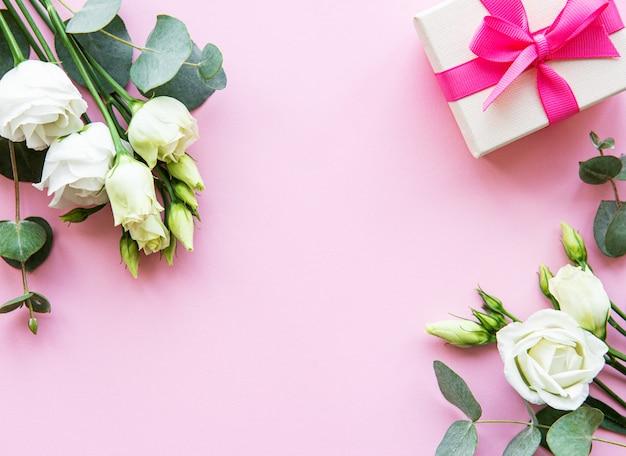 Flores de eustoma blanco y caja de regalo sobre fondo rosa