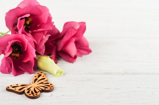 Flores de eustoma rosa púrpura y corazón de madera