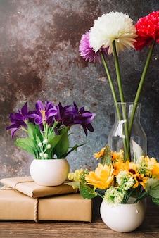 Flores falsas en diferentes tipos de jarrones con cajas de regalo envueltas contra el fondo del grunge