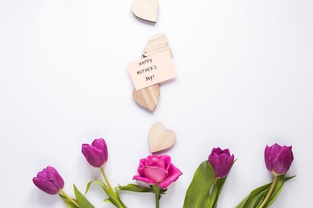 Flores con feliz dia de madres inscripción y corazones.