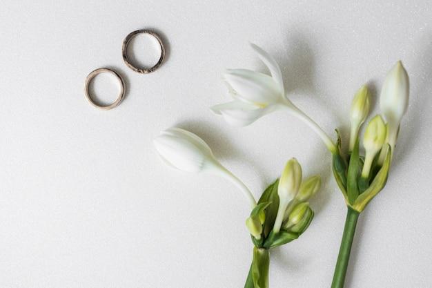 Flores florecientes con dos anillos de boda en el fondo blanco