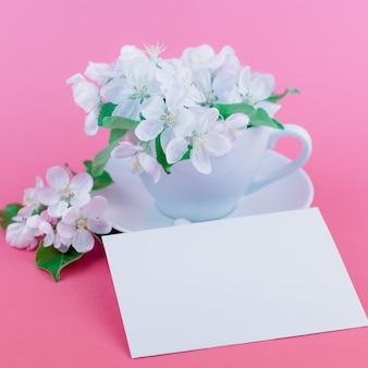Flores florecientes del manzano blanco de la primavera en una taza