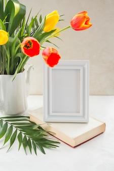 Flores en florero y marco de fotos colocados en una mesa cerca de la pared