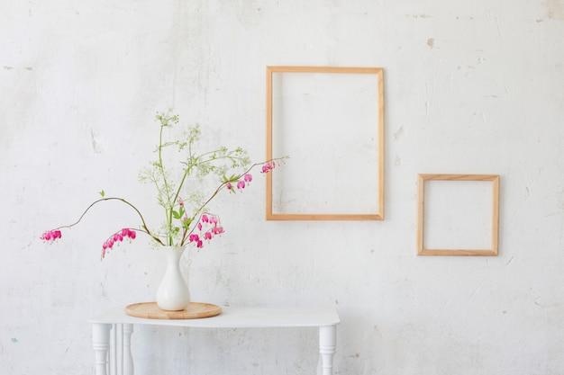 Flores en florero sobre fondo blanco de la pared