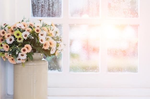 Flores en florero en la ventana