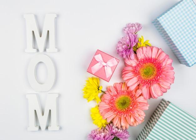 Flores frescas cerca de cajas presentes y palabra de mamá