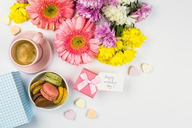 Flores frescas cerca de la etiqueta con palabras en presente, taza de bebida y macarrones en un tazón