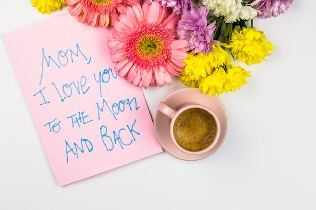 Flores frescas cerca de papel con palabras y taza de bebida
