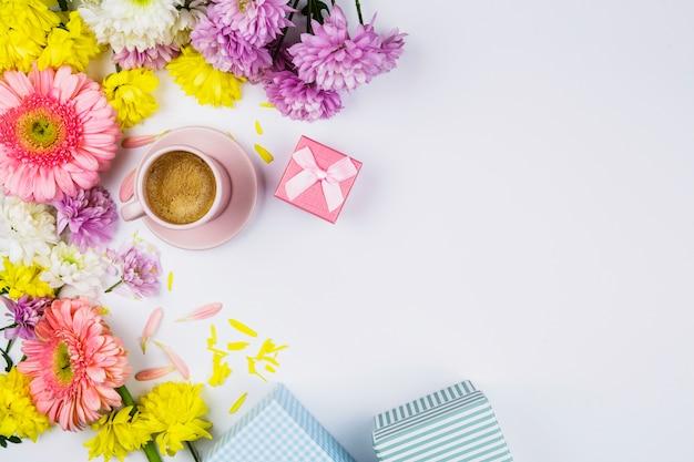 Flores frescas cerca de taza de bebida, cajas presentes y pétalos.
