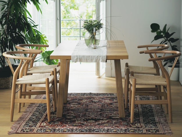 Flores frescas en florero de vidrio de pie sobre una mesa de madera en el interior del comedor blanco con alfombra oriental. diseño de interiores en estilo minimalista.