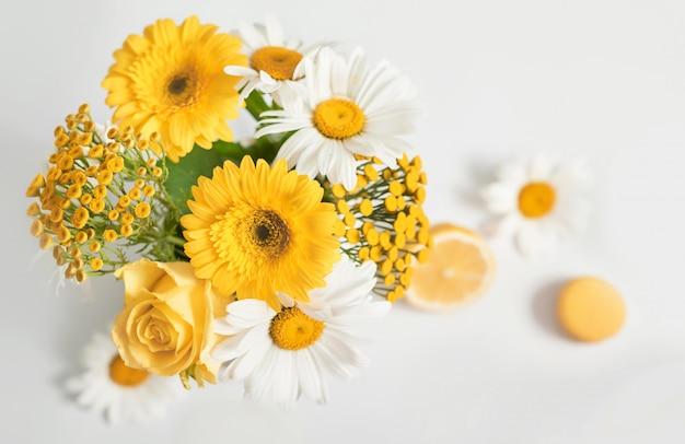 Flores frescas de manzanilla en un jarrón con limón y macarrón