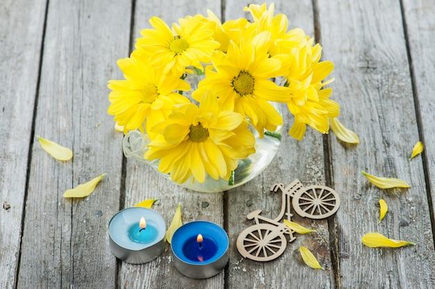 Flores frescas de margarita amarilla, bicicleta y velas encendidas