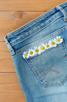 Flores frescas de margarita blanca en el bolsillo de los jeans.