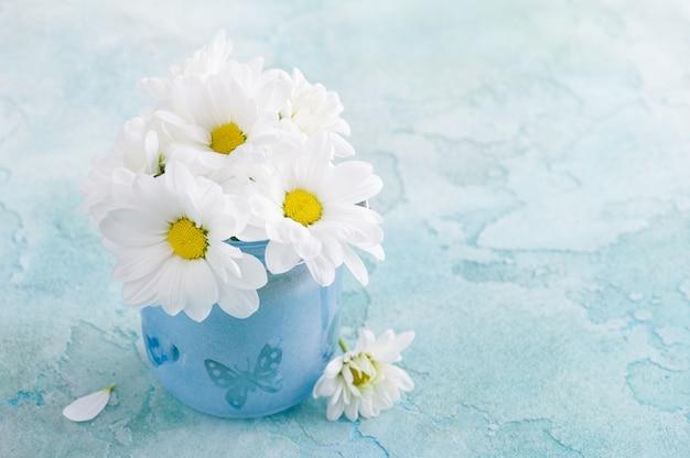 Flores frescas de margarita en vidrio azul