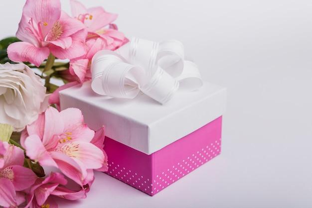 Flores frescas y presente caja sobre fondo blanco