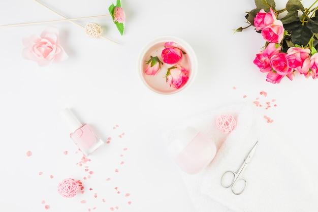 Flores frescas con productos cosméticos sobre fondo blanco.
