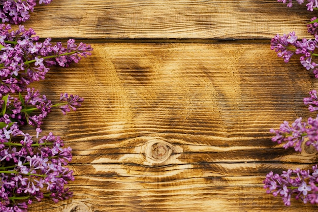 Flores frescas con ramitas y hojas de color lila verde se encuentran en una vieja madera exprimida